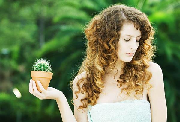 Девушка держит горшок с кактусом