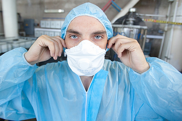 Человек в защитном халате и респираторе