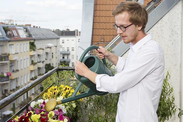 Мужчина поливает цветы на балконе